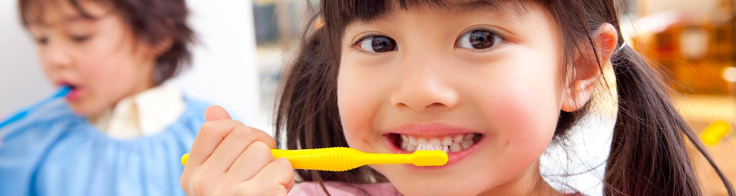 smiling asian preschooler smiling with yellow toothbrush on her teeth, blurred boy in background also brushing his teeth