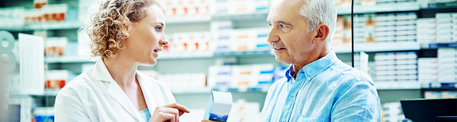 female pharmacist pointing to medication and talking with a senior male patient , pharmacy wall with medicine seen in background