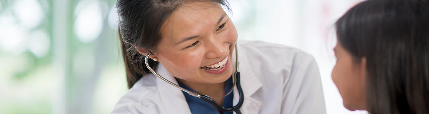young, Asian female doctor with stethoscope in her ears, smiling and looking at young girl with long brown hair