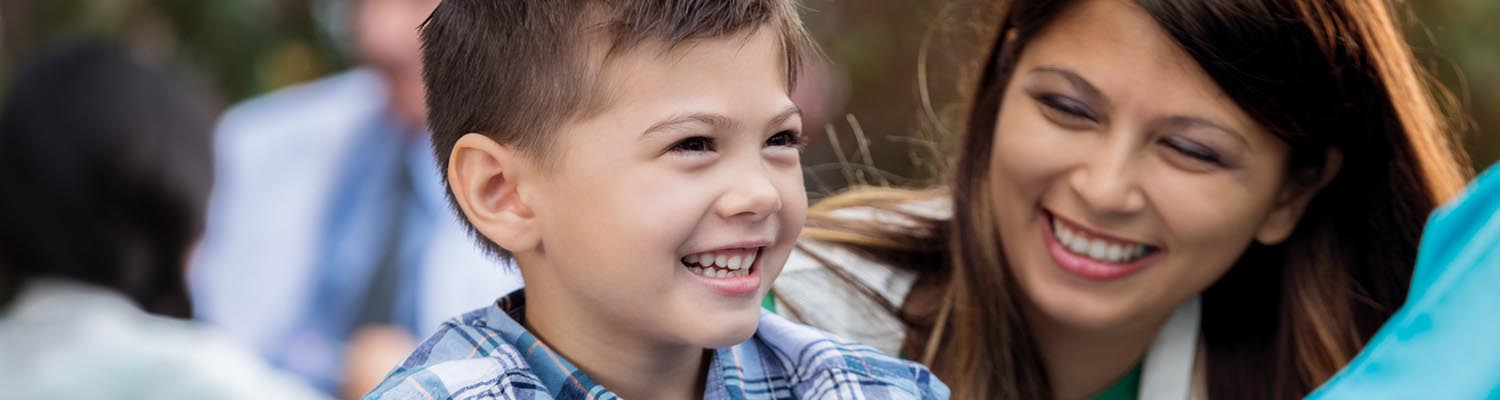 smiling young boy with mother to right looking at health care provider