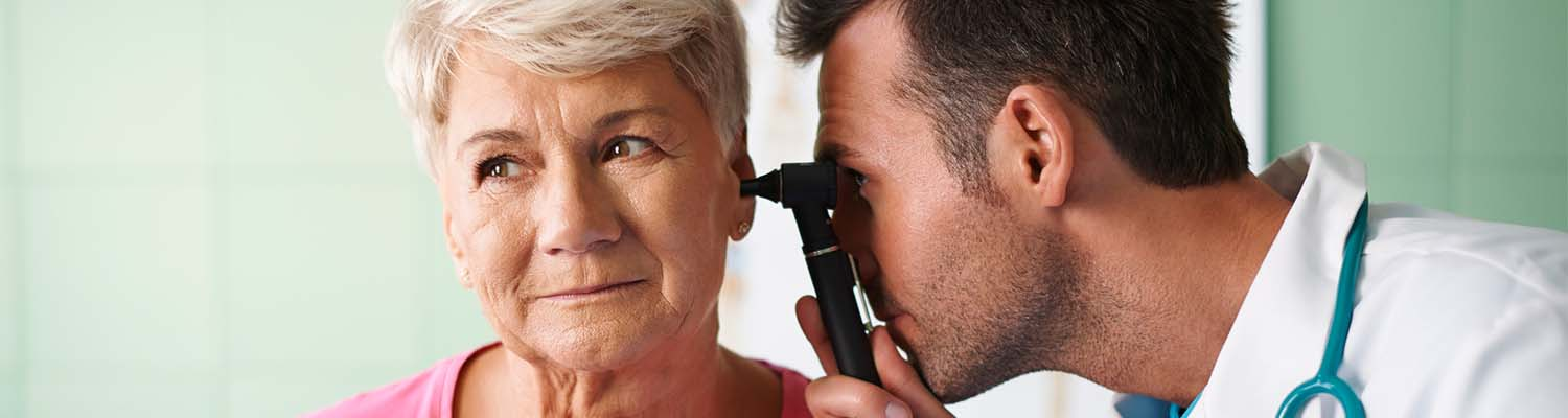 senior woman with white hair looking to the left, male doctor looking in her ear with a otoscope