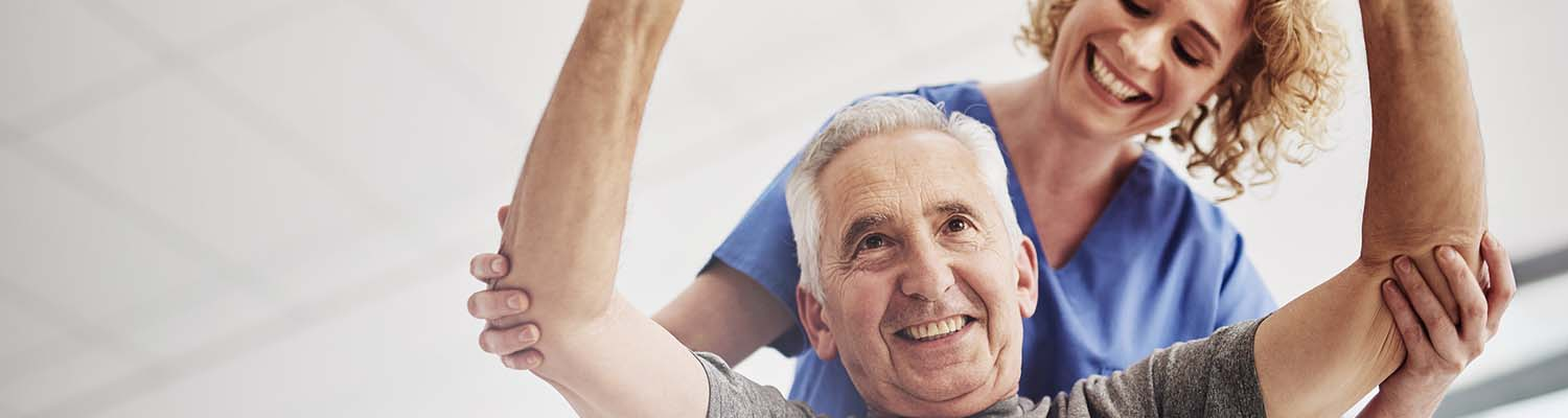 senior patient smiling, exercising with arms in air and nurse in background aiding his arms