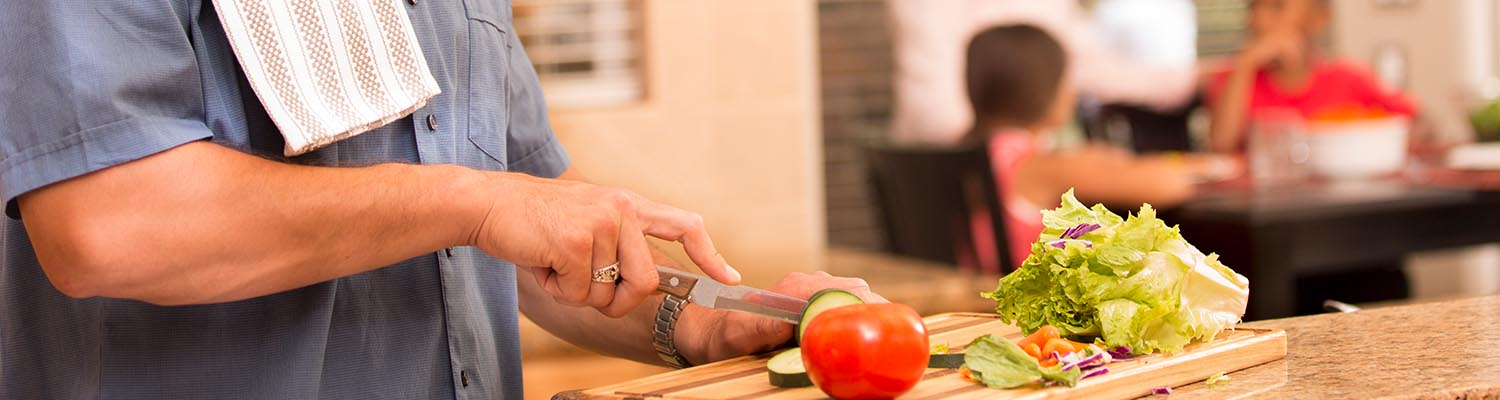 closeup of man's hands cutting vegetables, family at dinner table in background