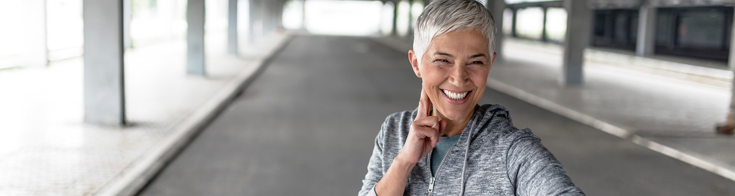 Mature, gray hair woman checking results after jog