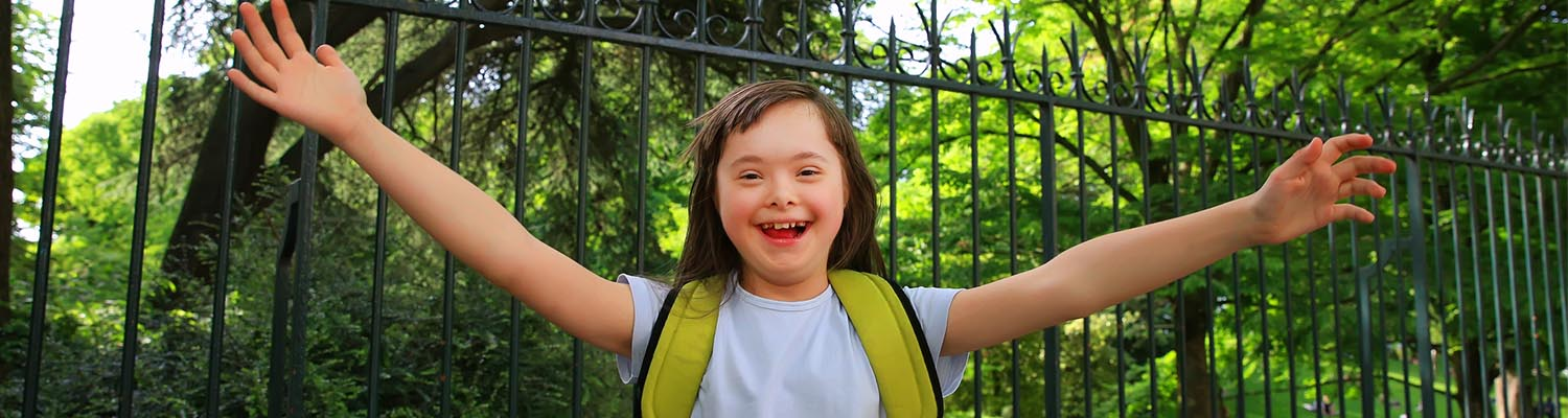 young girl with down syndrome and long brown hair, wearing backpack and smiling in park with beautiful green trees