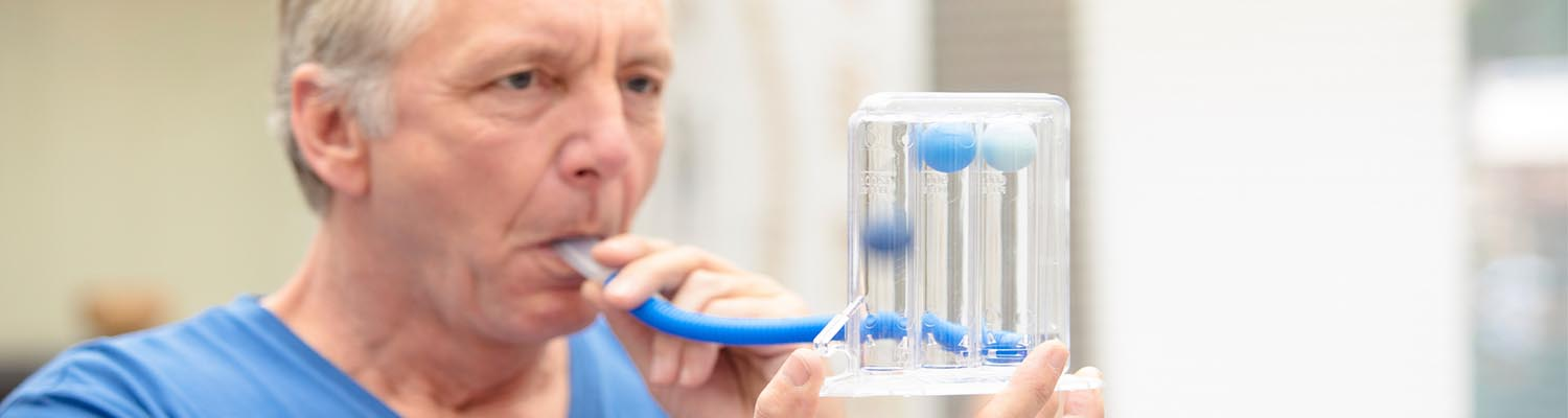 older man in blue t-shirt breathing into a tube connected to a spirometer