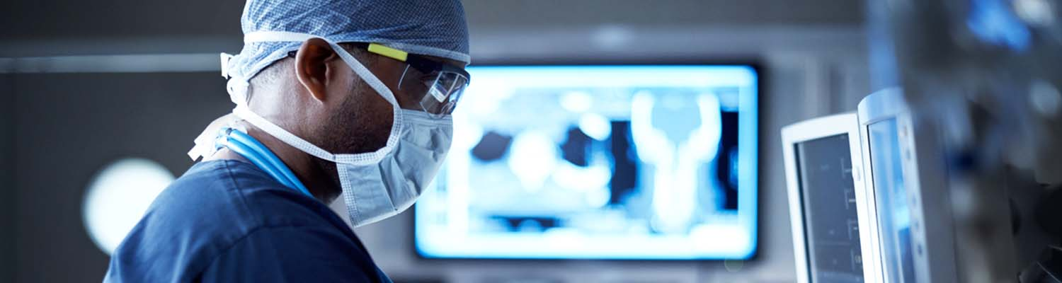Male surgeon wearing surgical mask and safety glasses looks a monitor, image from blurred monitor fills background