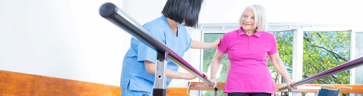 Senior woman using parallel bars to walk, smiling looking at nurse who is aiding her