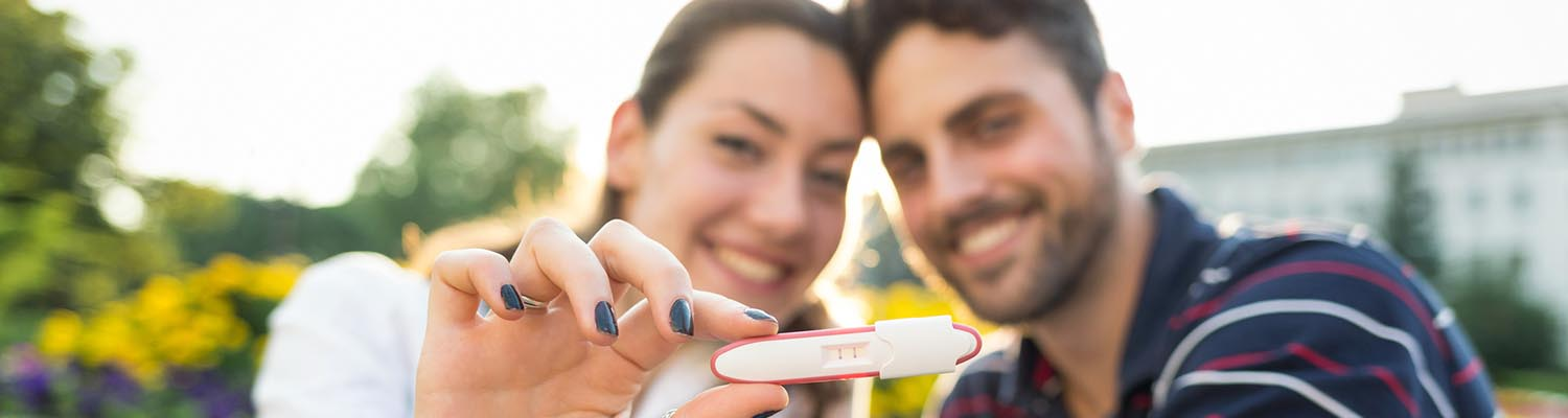 Young couple smiling and holding up a positive pregnancy test