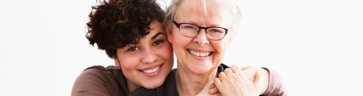 young woman embracing senior woman, both happy together