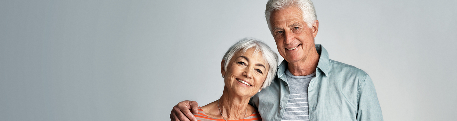 Middle age couple both man & woman have white hair, woman's head is tilted towards man