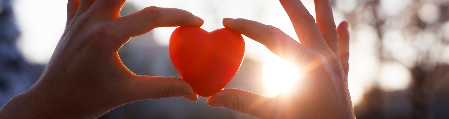 Closeup of woman's hands holding a red plastic heart, with sun light surronding