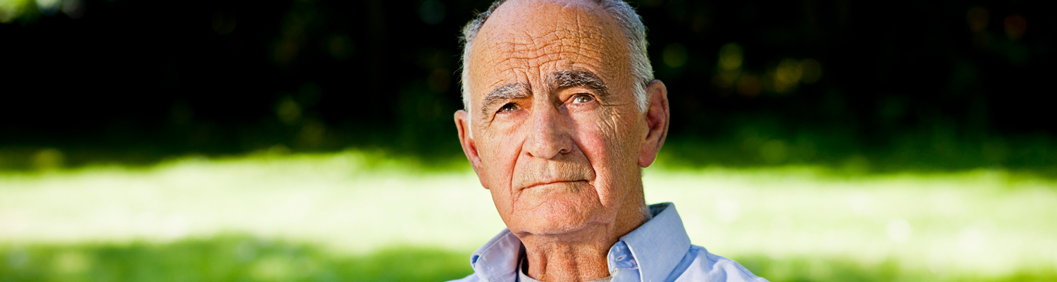 Older man with serious look sitting outdoors