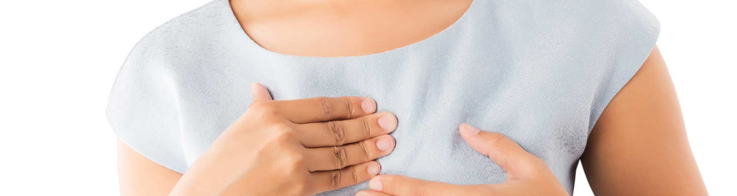 closeup of woman's hands holding chest as if in pain