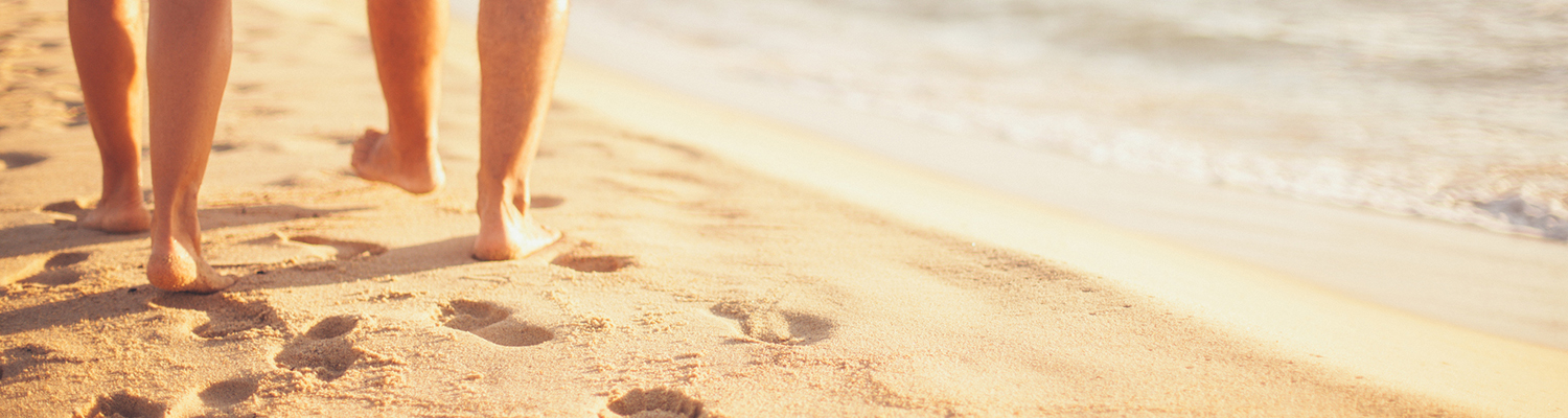 Closeup of back of man and woman's feet walking on beach near edge of ocean