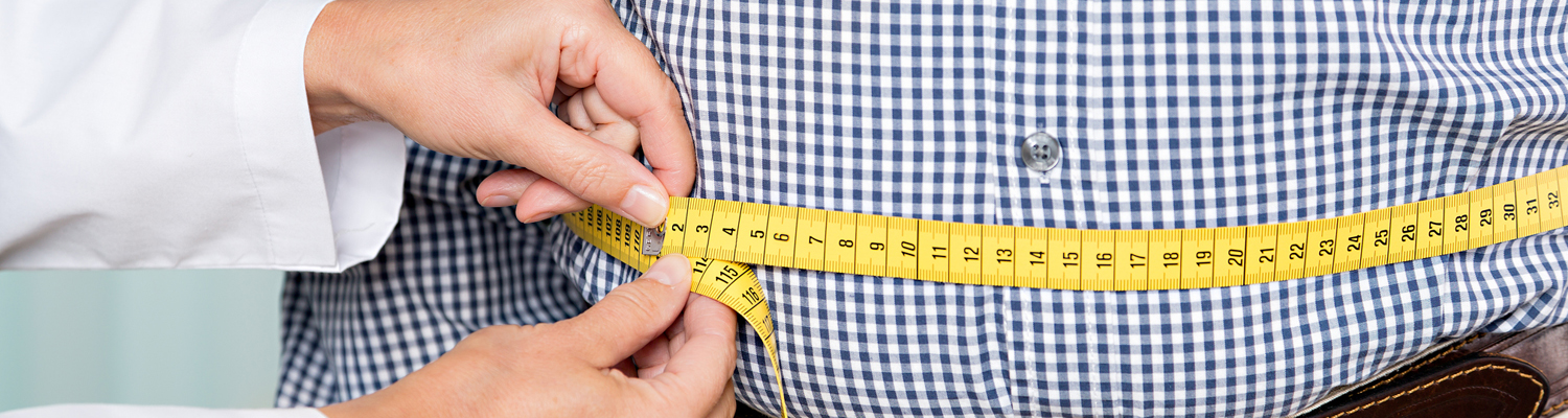 Doctors hands hold measuring tape around man's waist