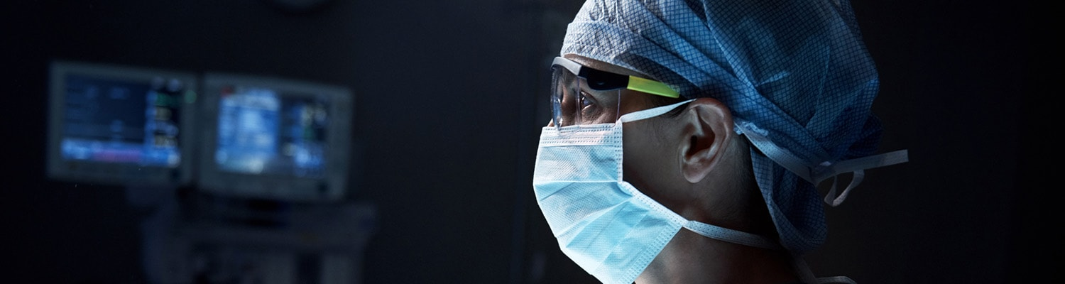 Surgeon in dark operating room with mask and protective glasses on looking at monitor.