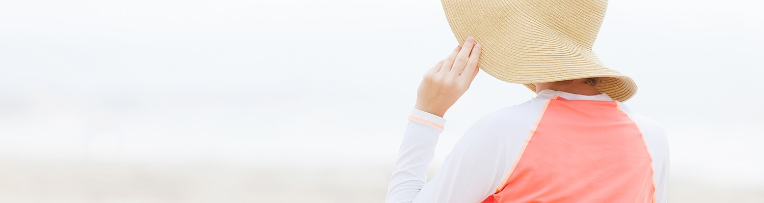 Back of woman at beach demonstrating sun protection with a floppy hat and a long sleeve shirt.