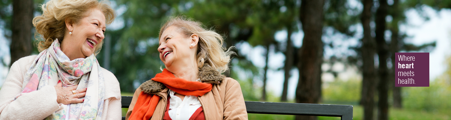 Two older female friends laughing on bench in the spring time