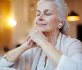 older woman, eyes closed, ear buds in